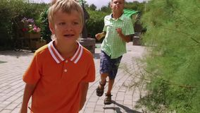 Two boys running in the park stock video footage