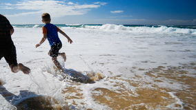 Two boys running and splashing in water on the beach. Two happy boys running and splashing in water on the beach stock footage