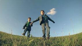 Two boys running together on green hill, slow motion stock video footage
