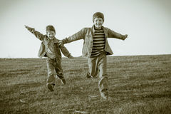 Two boys running together on meadow, sepia toned Stock Photos