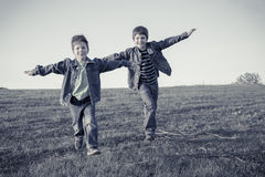 Two boys running together on meadow, sepia toned Royalty Free Stock Photo
