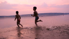 Two boys running together on river`s beach at sunset. Silhouette of two boys running together on river`s beach against sunset, slow motion stock video
