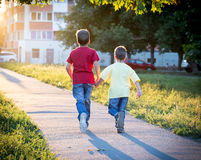 Two boys running together on street Royalty Free Stock Photos