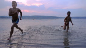 Two boys running from water against sunset. Silhouette of two boys running from water against sunset, slow motion stock footage