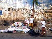 Two boys scavenge and look for recyclable things at a dump site Stock Photo