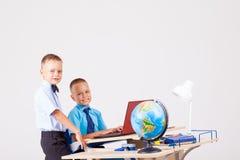 Two boys school computer desk globe Stock Photo