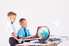 Two boys school computer desk globe. Education Royalty Free Stock Photo