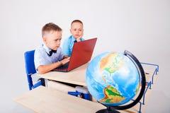 Two boys school computer desk globe royalty free stock photography