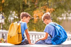 Two boys after school, sitting on bench and talking. Two kids after school, sitting on bench and talking stock photos