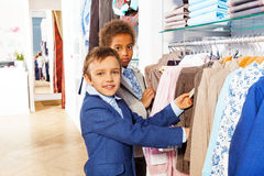 Two boys search clothes while shopping Royalty Free Stock Image