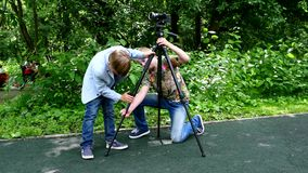Two boys set video camera on a tripod of green park background. stock video footage