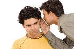 Two boys sharing secrets. Close-up of a man whispering confidentially into the ear of another man, both with happiness expressions royalty free stock photography