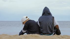 Two boys sit on the beach and look at the sea stock footage