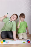 Two boys sit on floor and show their forefingers Stock Images