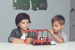 Two boys sit in a workshop at a gray table and create a merry-go-round. Two boys sit in a workshop at a gray table and create a carousel They made a miniature Royalty Free Stock Images