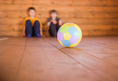 Two boys sittin on a floor with a ball Royalty Free Stock Photo