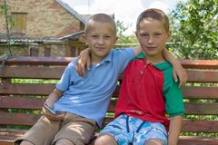 Two boys sitting on the bench,two brothers hugged sitting on the bench Stock Photos