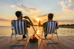 Two boys sitting on chairs and drinking beer on seashore at sunset. Stock Image
