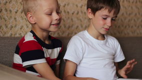 Two boys sitting on a  couch and read a book. Two boys sitting on a couch and read a book smiling stock video footage