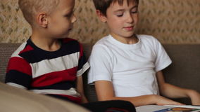 Two boys sitting on a couch and read a book. Smiling stock video