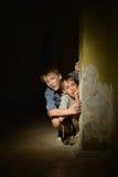 Two  boys sitting in a dark cellar Royalty Free Stock Image