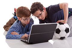 Two boys sitting on the floor playing computer, on Stock Photography