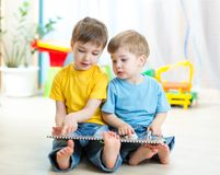 Two boys sitting beside him and read a book Stock Image