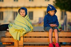 Two boys sitting and looking at sunrise Stock Image