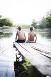 Two boys sitting on a pier Stock Photos