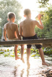Two boys sitting on a pier Royalty Free Stock Images