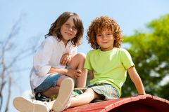 Two boys sitting on rooftop in park. Royalty Free Stock Photography