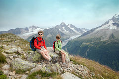 Two boys are sitting on slope of high mountain Stock Photo