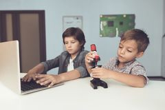 Two boys are sitting at the table. One of them is sitting in front of a gray laptop. The second stretches to microscope. Two boys are sitting at the table. One Royalty Free Stock Images