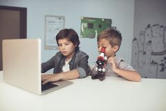 Two boys sitting at the table. One of them is sitting in front of a gray laptop. The second looks through a microscope. Two boys are sitting at the table. One of Royalty Free Stock Photos