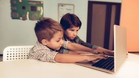 Two Boys Sitting at Table and Using Laptop at Home stock image