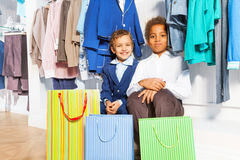 Two boys sitting under hangers with clothes Stock Images