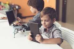 Two boys are sitting in the workshop at the table. One of them sits behind a laptop, the second with a tablet. Between them, the robot Stock Photos
