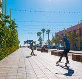 Two Boys skateboarding In Santa Monica. Two skateboard buddies heading to the beach in Santa Monica, California in front of the world famous Santa Monica Pier Stock Photo