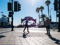 Two Boys skateboarding In Santa Monica. Two skateboard buddies heading to the beach in Santa Monica, California in front of the world famous Santa Monica Pier Stock Photography
