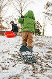 Two boys sledding on hill Royalty Free Stock Image