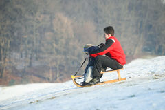 Two boys sledding on hill Stock Photo