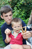 Two boys with a slingshot. Teenager and little boy with a slingshot Royalty Free Stock Image
