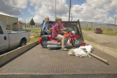 Two boys on a small motorcycle, in Lima Montana Stock Photo