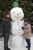 Two boys and a snowman. Two boys playing with a big snowman stock photos