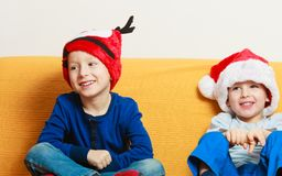 Two boys on sofa wearing christmas hats Royalty Free Stock Image