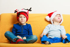 Two boys on sofa wearing christmas hats Royalty Free Stock Photography