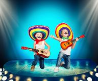Mexican party.Two boys in sombrero with a guitar on stage.Mexican macho. Two boys in sombrero with a guitar on stage.Mexican macho.Mexican party stock photo
