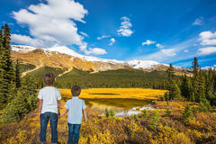 Two boys stand on the coast of the marshy lake stock photo