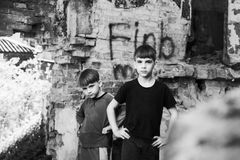 Two boys stand in a destroyed and abandoned building, black and white photo. Staged photo stock images