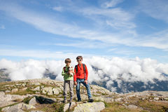 Two boys stand on top in high mountain Stock Image